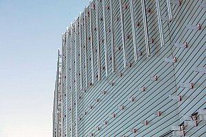 Les toits en « shed » rappellent l'histoire industrielle du site via la forme des charpentes des hangars industriels. L'aluminium et le verre, matériaux choisis pour habiller la toiture et les extérieurs du bâtiment, alternent bandes opaques et vitrées. Le bardage définitif sera posé d'ici quelques jours - © Tommaso Morello